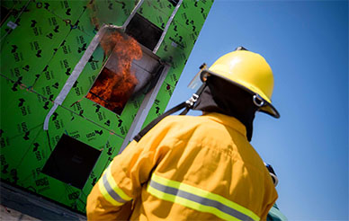 A firefighter looks on as researchers conduct fire tests on a building that has just undergone a simulated earthquake on UC San Diego's shake table. Photo by Erik Jepsen/UC San Diego Publications